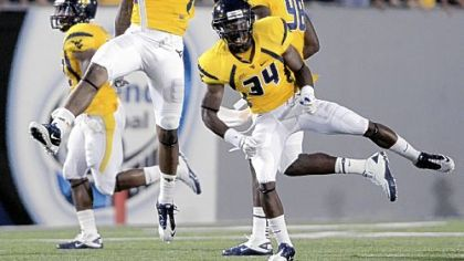 West Virginia's Bruce Irvin (11) and Ishmael Banks (34) celebrate a defensive play against Marshall in the third quarter Sunday at Mountaineer Field.