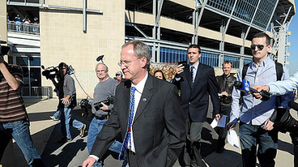 Penn State sports information director Jeff Nelson walks away from the media outside the Beaver Stadium after announcing the cancellation of Coach Joe Paterno's weekly press conference.
