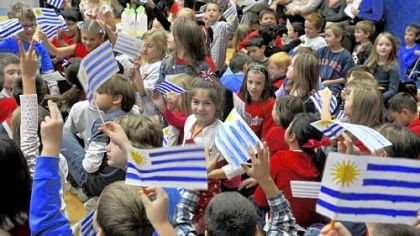 Waving their Uruguayan flags during an assembly, Howe Elementary students welcome two fifth-grade students and their teacher, who have been pen pals.
