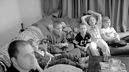 Bob plays a video game with Robert Jr., (third from left), while Raine, Ashton, Laurel and Autumn watch.