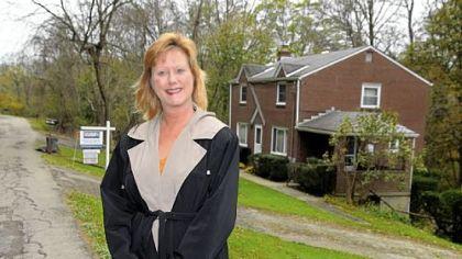 Margie Churchel with one of her listed houses in Penn Hills.