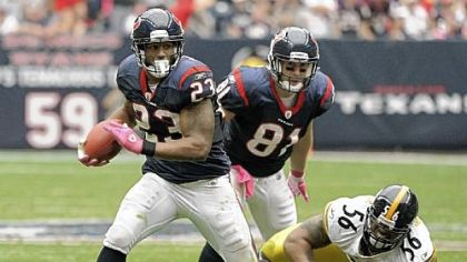 The Texans' Arian Foster (23) breaks away from Steelers outside linebacker LaMarr Woodley Sunday.
