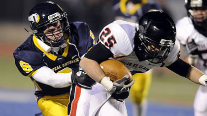 Upper St. Clair's A.J. McGuire carries as he's defended by Central Catholic's Leo Loughery last night.
