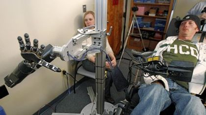 Assistant professor Jennifer Collinger, left, watches as quadriplegic research subject Tim Hemmes operates the mechanical prosthetic arm in a testing session at UPMC.