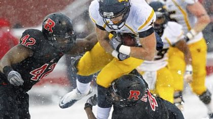 West Virginia's Tyler Urban tries to split two Rutgers defenders Saturday in the snow of Piscataway, N.J.