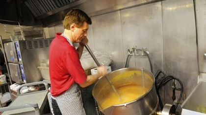Jim Calato stirs a steam-jacketed kettle of gravy in preparation for the annual Thanksgiving lunch at the City Deli.