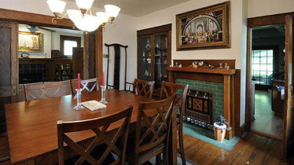 The dining room features a decorative fireplace with forest green tile and a hefty oak mantelpiece.
