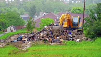 A backhoe sits atop rubble remains of a recently demolished house just west of Buckhannon Pike in Clarksburg, W.Va.