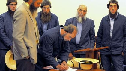 In a file photo, Johnny Mullet signs documents during a preliminary hearing in October in the Holmes County Courthouse in Millersburg, Ohio. In the foreground is his attorney, Andy Hyde, and behind him, from left to right, are Lester Mullet, Daniel Mullet, Levi Miller and Eli Miller.