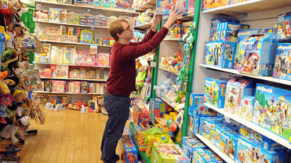 Derek Fisk stacks toys at Fun Buy the Pound in Robinson Mall. The store is sticking to its current crew and just giving them extra hours to meet the holiday rush.