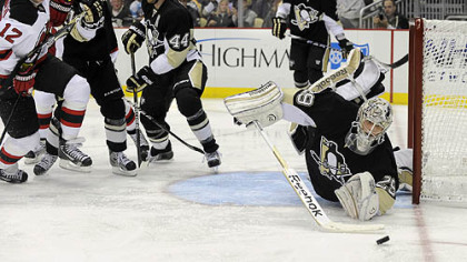 Penguins&#039; Marc-Andre Fleury dives to knock the puck away against the Islanders.