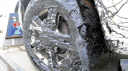 A vehicle's tire is shown covered in a tar-like chemical Wednesday near Oakmont.