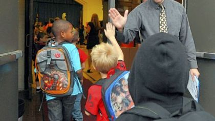 George Washington Elementary principal Paul Sweda gives high-fives to students Thursday as they arrive for the first day of school.