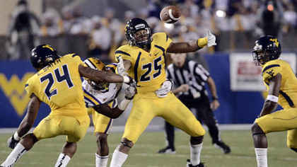 West Virginia's Darwin Cook, middle, looks to corral a loose ball in the Mountaineers' game vs. No. 2 LSU Saturday night.