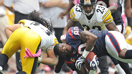 Steelers safety Troy Polamalu knocks the helmet off Texans receiver Andre Johnson.