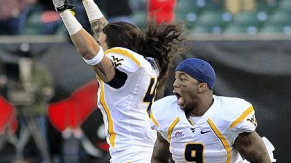 West Virginia's Vernard Roberts, right, and Matt Moro celebrate their dramatic victory Saturday in Cincinnati. Eain Smith blocked a field-goal attempt that would have tied the score.