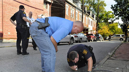 Pittsburgh Police detective John Rouse and Pittsburgh Police officer Jason Hall look in a sewer for a gun that was used in a Monday morning shooting at the corner of Armandale Street and Brighton Road on the North Side.
