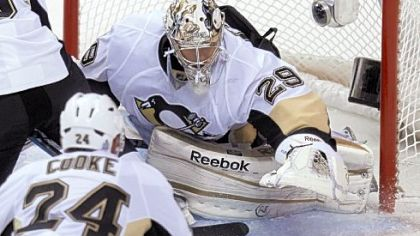 Goalie Marc-Andre Fleury reaches down to smother the puck as Matt Cooke looks on in the second period Thursday in the season opener against Vancouver.