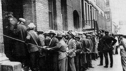 Men wait outside an unemployment relief registration center in New York City during the Great Depression.