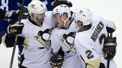 Penguins left wing Matt Cooke, center, celebrates his first-period goal with teammates Pascal Dupuis (9) and Matt Niskanen (2) during season opener against Vancouver.
