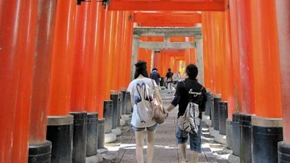 Visitors to Fushimi-Inari Taisha pass under thousands of orange gates en route to a shrine near Kyoto, Japan.