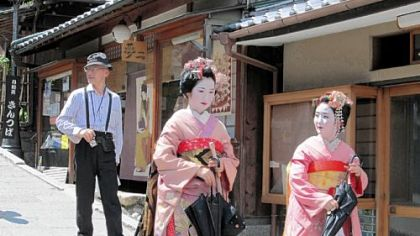 Maiko, geishas in training, are sought after by tourists for photos as they walk through Kyoto.